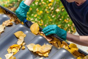 Man cleaning clogged gutters