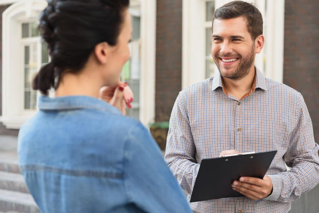 Man with Clipboard Smiling at Woman