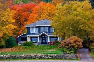 Blue house surrounded by fall foliage