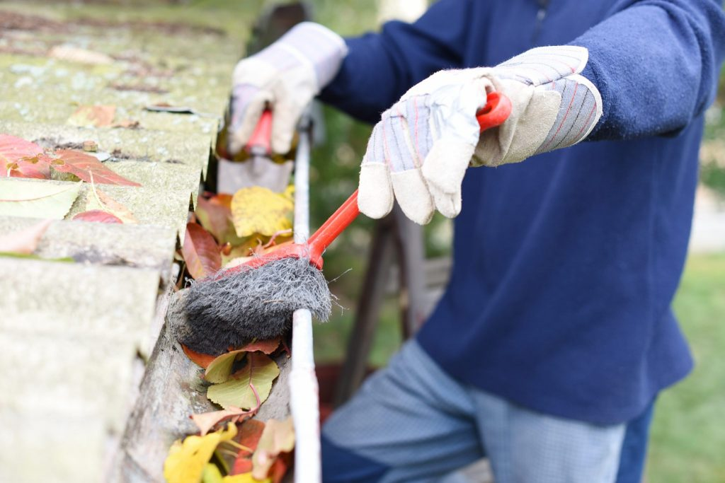 Man cleaning out a gutter with a brush